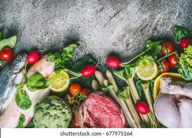 Healthy balanced eating and diet nutrition concept. Various organic foods ingredients: fish,meat,poultry,chicken,vegetables and greens seasoning on gray stone background, top view, border