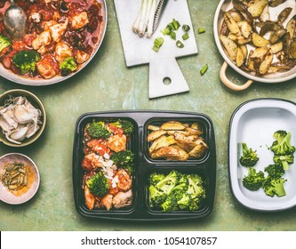 Healthy balanced lunch box preparation with chicken pieces in tomatoes sauce with green broccoli and  baked potatoes, top view