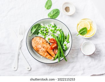 Healthy balanced meal lunch plate - baked salmon with rice and vegetables on a light background, top view