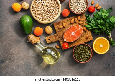 Healthy balanced nutrition concept, salmon,legumes, fruits, vegetables, olive oil and nuts, dark rustic background. Top view, copy space