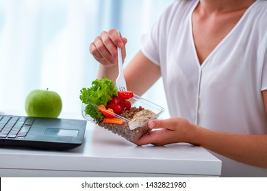 Healthy balanced snack at office workplace. Business woman eating meals from lunch box at working table during lunch time. Food at work