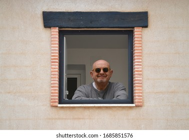 Healthy Bald Senior Man at his window in isolated during COVID-19 Pandemic illness in Spain