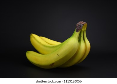 Healthy bananas isolated on black background