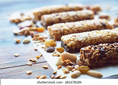 Healthy bars with nuts, seeds and dried fruits on the wooden table, with copy space.