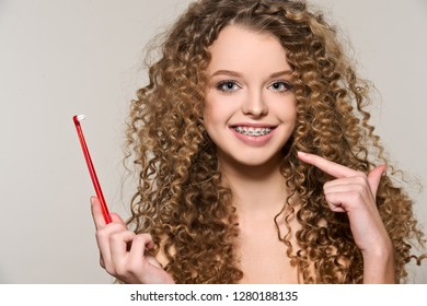Healthy, beautiful smile, cute teen  with dental braces smiling . Portrait of a girl with orthodontic appliance. Girl brushing her teeth with toothpaste.