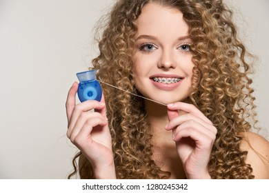 Healthy, beautiful smile, cute teen  with dental braces smiling . Portrait of a girl with orthodontic appliance. Girl brushing her teeth with dental floss.