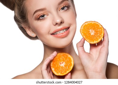 Healthy, beautiful smile, cute teen  with dental braces smiling . Portrait of a girl with orthodontic appliance and tangerine .