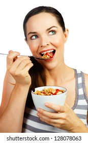 Healthy beautiful woman eating a nice bowl of cereal and strawberries for breakfast. Isolated on white.