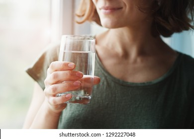 Photo of healthy beautiful young woman holding glass of water