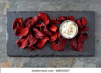 Healthy beet chips with dip, above view on a stone server and slate background