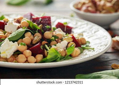 Healthy Beet Salad with chickpeas, pistachios nuts, feta cheese on rustic wooden background