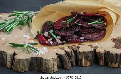 Healthy beetroot chips  with salt and rosemary. Snack for gourmets. Baked beet slices.Selective focus