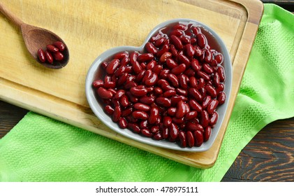 Healthy Benefits of Red beans. Red beans in shape-heart dish and wooden spoon on wooden broad.