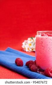 A healthy berry drink - raspberry smoothie on red