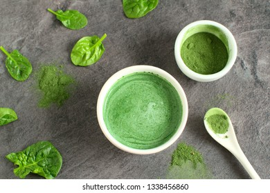 Healthy beverage made from green raw ingredients on a dark gray background