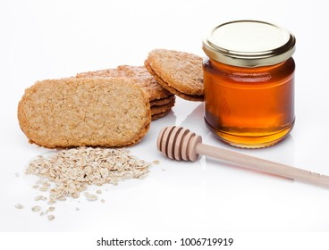 Healthy bio breakfast grain biscuits with honey and raw oat porridge on white background