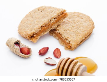 Healthy bio breakfast grain biscuits with honey and peanuts on white background