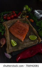 Healthy Bio Salmon Fillet with spices, herbs, vegetables on a Wooden Background. Cooking Concept. Dinner preparation.