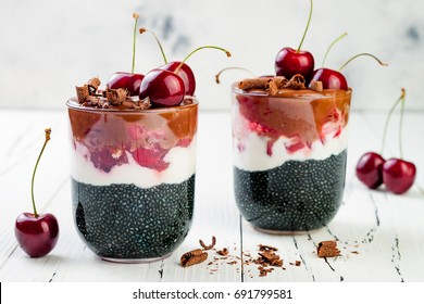 Healthy Black Forest dessert. Black activated charcoal chia pudding with cherries, coconut cream and chocolate. Vegan creamy breakfast.