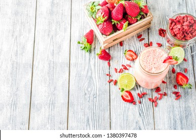 Healthy blended drink. Organic diet smoothie with lime, strawberry and goji berries, wooden background copy space