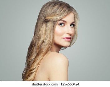 Healthy blonde woman portrait. Girl with long curly hair and clear skin, skincare and wellness concept