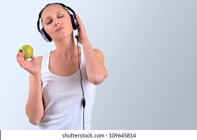 Healthy blondy happy woman holding a green apple and listening to music