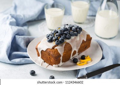 Healthy Blueberry Loaf Cake on white plateTopped with Icing Sugar Glaze and Fresh Berries.