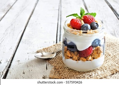 Healthy blueberry and raspberry parfait in a mason jar on a rustic white wood background