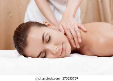 Healthy body. Close-up of female hands giving massage with oil to a young brunette in spa salon