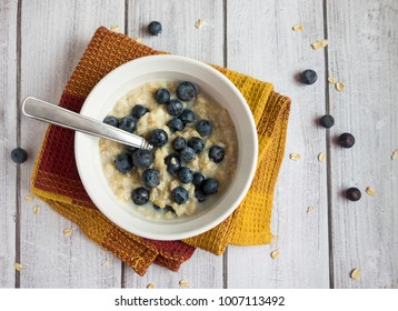 A healthy bowl of hot oatmeal with blueberries with spoon sitting on a light wood surface.