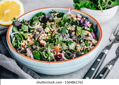 Healthy bowl kale and quinoa salad with dry cranberries, red onions and almonds