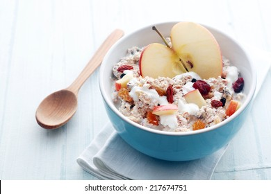 Healthy bowl of muesli, apple, fruit, nuts and milk for a nutritious breakfast with a low glycemic index ensuring plenty of energy for the day