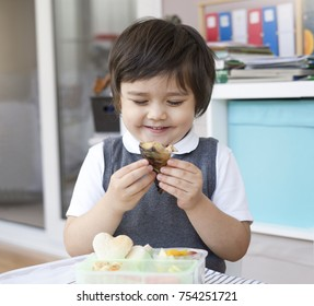 Healthy boy enjjoy having healthy food, fish, bread toasted with honey and fruit salad for his lunch, School boy with happy face eating lunch box, Healthy food or Lunch box at school concept