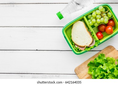 healthy break with lettuce, grape and sandwich in lunchbox on home table flat lay mock-up