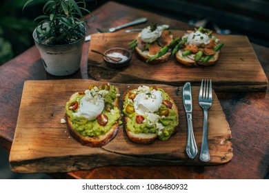 Healthy breakfast. Avocado toasts with salmon, asparagus and poached eggs
