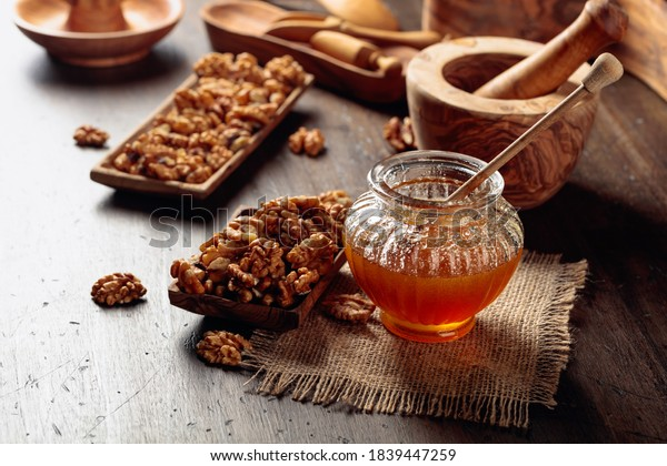 Healthy breakfast background. Honey and walnut on a old wooden table.
