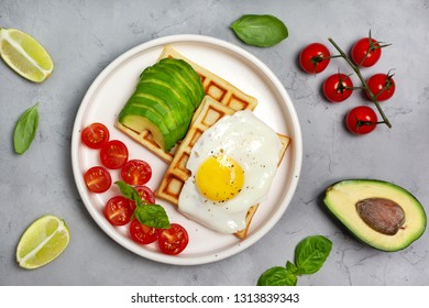 healthy breakfast. belgian wafers with avocado, fried egg, cherry tomatoes on a gray concrete background. view from above