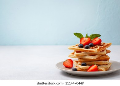 Healthy breakfast. Belgian waffles with fresh berries: blueberries and strawberries, mint on a light background