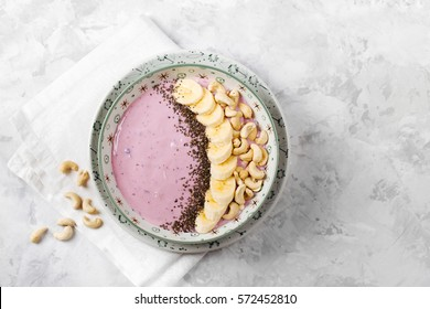 Healthy breakfast  berry smoothie bowl topped with banana, cashew and chia seeds with copy space