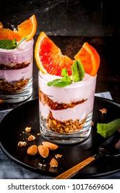 Healthy breakfast, Blood Orange Parfait with granola. yogurt, almond and mint, dark rusty background, copy space