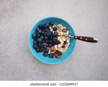 Healthy breakfast in a blue bowl. Oatmeal with blueberries and nut mix. Healthy food concept on a grey concrete background . Top view, side view. Space for text.
