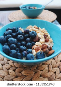 Healthy breakfast in a blue bowl. Oatmeal with blueberries and nut mix. Healthy food concept. Top view, side view. Space for text.