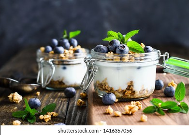 Healthy breakfast of blueberry parfaits made with fresh fruit, Greek yogurt,  and granola over a rustic cutting board and table. Selective focus on glass jar in front with blurred background.
