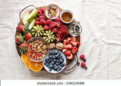 Healthy breakfast board included granola, fruits and berries selection, nuts and honey. Plant based, clean eating, super food, vegetarian concepts.