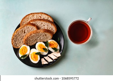 Healthy breakfast. Boiled eggs, bread, butter, greens and tea