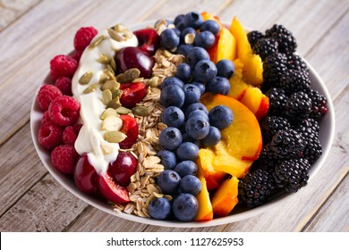 Healthy breakfast bowl - berries, muesli, fruits, yogurt and sunflower seeds. Healthy detox morning meal