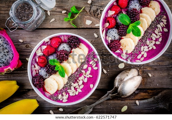 Healthy breakfast bowl: blueberry smoothie with banana, raspberry, pitaya, blackberry, almonds, sunflower and chia seeds