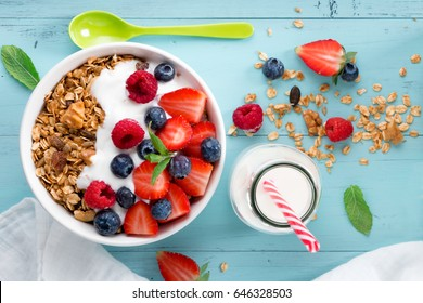 Healthy breakfast in a bowl with homemade baked granola, frozen berries, fresh strawberries, a bottle of milk and yogurt on a turquoise wooden table