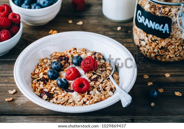 Healthy breakfast bowl. Homemade granola with natural yoghurt, blueberries and raspberries on a wooden rustic background