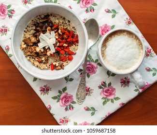 Healthy breakfast bowl. Milky quinoa porridge with goji, coconut, figs and nuts. Cup of cappuchino coffee. Selective focus, top view